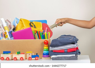 Donation concept. Person hand preparing donate box with books, pencils and school supplies for donation