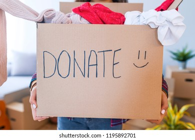 Donation Concept. Woman holding a Donate Box with full of Clothes. Woman holding a book and clothes donate box. Clothes in box for concept donation and reuse recycle