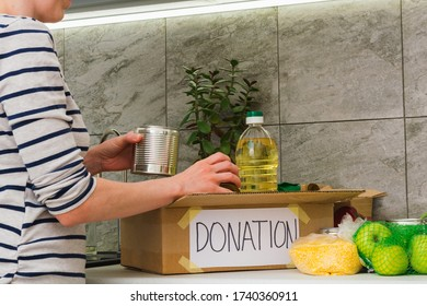Donation food in cardboard box with woman in kitchen. Help for people in quarantine time. Charity concept. Female collects products in box