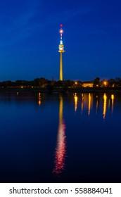 Donauturm in Vienna reflecting on danube river during night