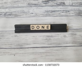 Done in letters on black rails with white wooden background