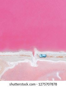 Done view from above to the Hutt Lagoon  Yallabatharra, Western Australia with blue car riding through the red, pink salt lakes near pink divided road river.