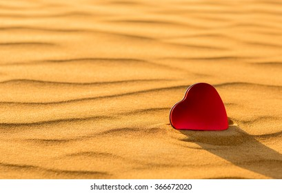 done-Closeup of heart shaped red tin in the golden desert sand.