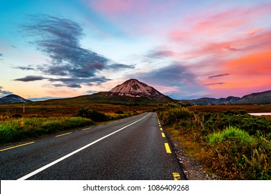 Donegal, Ireland. Mountain Errigal in Donegal county, Ireland in the evening at sunset with highway and colorful sky