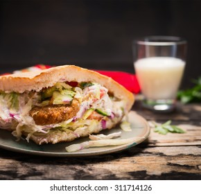 doner kebab with meat, sauce and vegetables with a glass airan on a plate On wooden rustic background, close up
