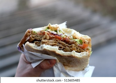 Doner kebab stuffed into a pita with tomatoes, cabbage and lettuce. Eating outdoor. Selective focus.