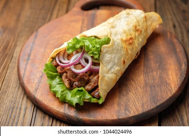 Doner wrap kebab is lying on the cutting board. Shawarma with meat, onions, salad lies on a dark old wooden table.