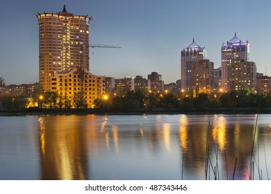 Donetsk City downtown skyline at dusk with skyscrapers illuminated over Kalmius river. Modern skyscrapers, new building construction, lights and reflections at water.