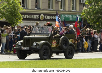 Donetsk People Republic, Ukraine. 2016, May 9. - Russian military veterans of World War II riding in the old car along Artema street during Victory Parade in Donetsk. Crowd, Flowers, Flag of Russia.