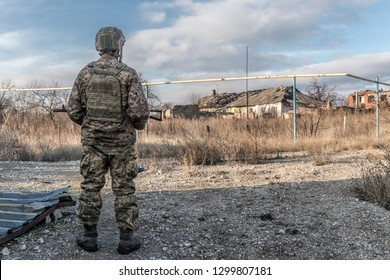 Donetsk region. Ukraine. 12.13.2018.  A soldier dressed in military uniform with a machine gun stands on the road and looks at houses (buildings) destroyed by hostilities.