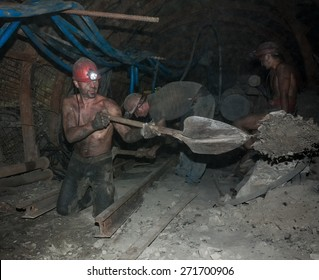 Donetsk, Ukraine - August, 16, 2013: Miners perform heavy manual labor in low light conditions and dusty. Mine is named Chelyuskintsev