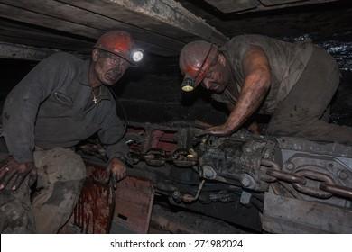 Donetsk, Ukraine - August, 16, 2013: Miners near the coal mining shearer. Mine is named Chelyuskintsev