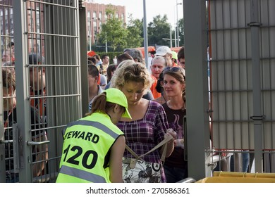 DONETSK, UKRAINE - JULY 10: Unidentified female steward checks the fans-women at the entrance to the stadium Donbass Arena on July 10, 2011 in Donetsk. Before the match of the Championship of Ukraine