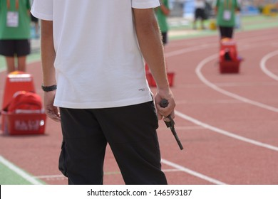 DONETSK, UKRAINE - JULY 11: Official with starting pistol before the 110 meters Hurdles competition during 8th World Youth Championships in Donetsk, Ukraine on July 11, 2013