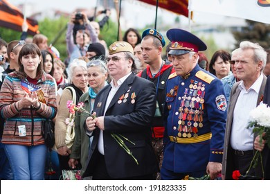 """DONETSK, UKRAINE - MAY 9: Supporters of the Donetsk People's Republic, during celebration of the Victory Day near """"To Donbass Liberators"""" monument in Lenin Comsomol park, on may 9, 2014 in Donetsk."""
