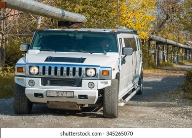 Donetsk, Ukraine - October 22, 2013: White Hummer H2 limousine at the rural street.