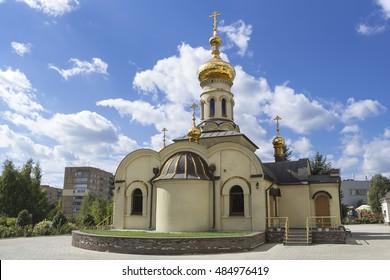 Donetsk, Ukraine - September 18, 2016: Temple of Xenia of St. Petersburg. Orthodox church. Golden domes and crosses under blue sky.