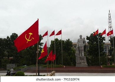 Dong Ha, Vietnam - September, 2015: City square with vietnamese and communist flags and stone monument of communist leader. Socialism symbol sickle and hammer