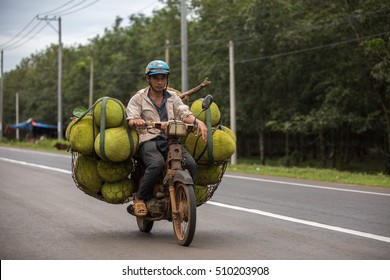 DONG NAI PROVINCE, VIETNAM - NOVEMBER 3: Unidentified man transporting jackfruits on an overloaded scooter in Dong Nai Province, Vietnam on November 3.