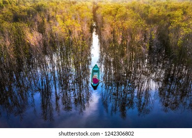 DONG THAP, VIET NAM - NOV 06, 2018: Aerial view of Vietnamese woman on boat at Tram Chim national parks, Mekong Delta, canal through melaleuca forest, nice scenery make wonderful place for ecotourism
