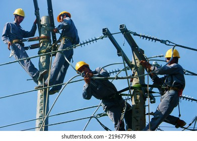 DONG THAP, VIET NAM- SEPT 23: Group Asian electrician climb high in pole to work, lineman with cable network, man repair electric post with belt safety, is industry service, Vietnam, Sept 23, 2014