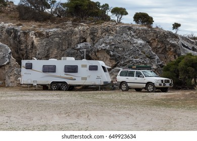DONGARA, WESTERN AUSTRALIA - MAR 1 2015: Large white offroad caravan and four wheel drive vehicle camped adjacent to coastal cliffs and a calm sea at the free camp site Cliff Head.