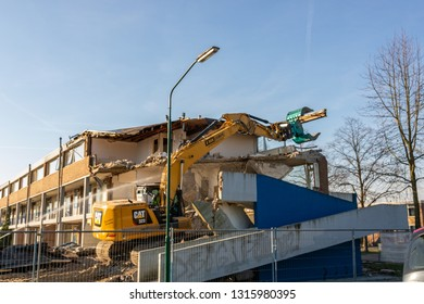 Dongen, The Netherlands - Februari 18, 2019: demolition crane demolish an old apartment building at trappistenstraat in Dongen. making room for new homes.