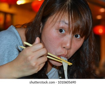 DONGHUAMEN, BEIJING, CHINA - JULY 6, 2012: Young Chinese woman eats noodles with chopsticks from a plastic bowl at Beijing's famous Donghuamen night market (tourist attraction), on July 6, 2012.