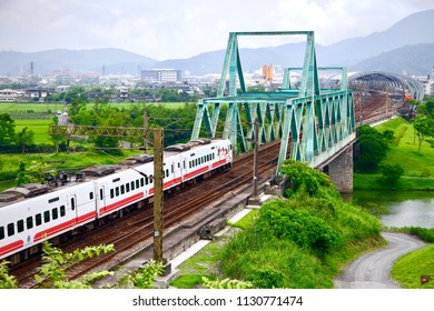 Dongshan Township / Taiwan - May 8, 2016: The Puyuma Express of Taiwan Railways Administration is going to pass through the green steel bridge and to stop at Dongshan Station in Yilan, Taiwan