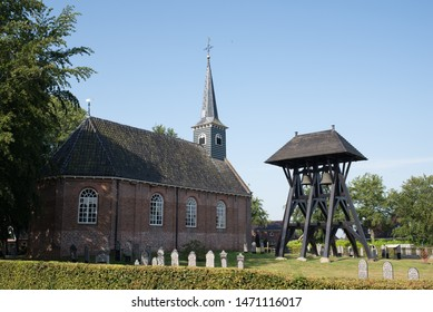 Donkerbroek, Friesland/Netherlands 07-21-2019: Historic bell cage beside old Laurens Church in the village Donkerbroek, Friesland, Netherlands. Cage with two bells from the Middle Ages.
