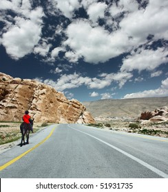 Donkey with boy walking on asphalt road under blue sky with clouds