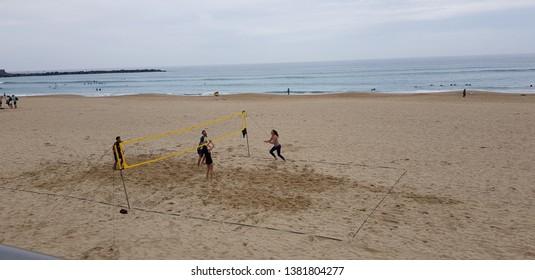 Donostia San Sebastian, Guipuzcoa, Basque Country, Spain, April, 13, 2019: Boys against girls playing beach volleyball at the Zurriola beach in the neighborhood of Gros in Donostia San Sebastian