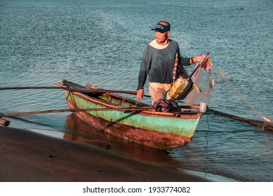 Donsol, Sorsogon, Philippines - June 19, 2007:  A fisherman pulls up his fishing net by the shore.