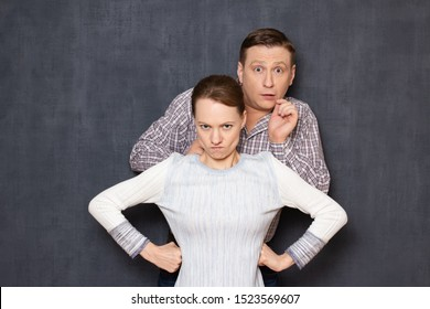 Don't be afraid, I defend you! Studio waist-up shot of brave fearless serious short woman guarding scared perplexed tall man, hiding before her back, seeing something awful. Relationship concept