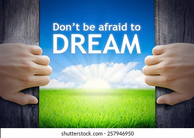 Don't be afraid to Dream. Hand opening an old wooden door and found Don't be afraid to Dream word floating over green field and bright blue Sky Sunrise.