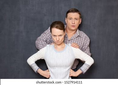 Don't be afraid and don't worry, I defend you! Studio half-length shot of brave fearless short woman guarding tall terrified man hiding before her back, seeing something awful. Relationship concept