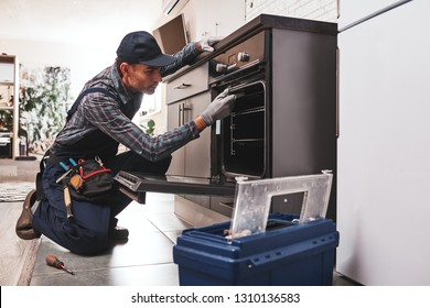 Don't delay with repair. Close-up of repairman examining oven with screwdriver in kitchen with tool case