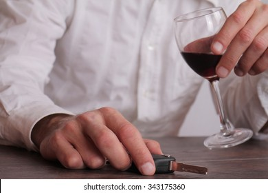 Don't drink and drive concept. Close up of man hand drinking wine and holding car keys. Responsibly and safety driving