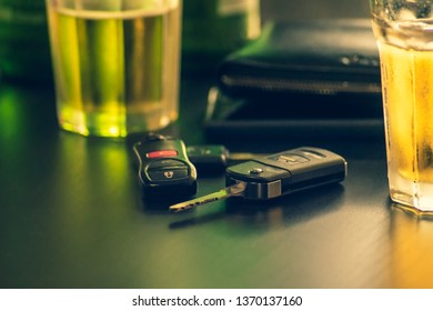 Don't drink and drive concept.remote Car key and glass beer or alcoholic beverage on wooden table in bar. takes roughly 30 minutes to2hours for alcohol to be absorbed into bloodstream. selective focus