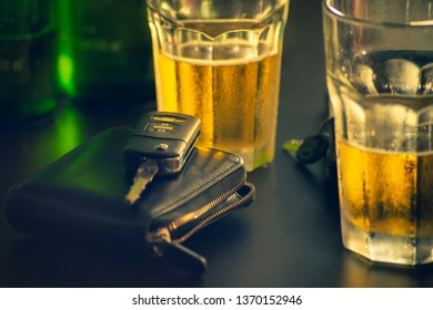 Don't drink and drive concept.remote Car key and glass beer or alcoholic beverage on wooden table in bar.takes roughly 30 minutes to2hours for alcohol to be absorbed into bloodstream. selective focus.
