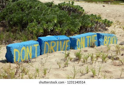 """Don't drive on the Beach"" written in yellow on blue bricks"
