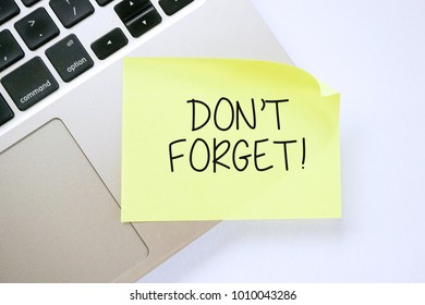 Don't Forget! on sticky note pasted on keyboard. Top view design