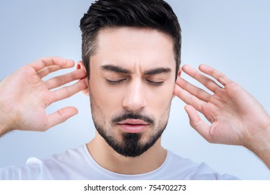 Dont hear. Emotional offended young man standing with his eyes closed and pretending not to hear the arguments of his girlfriend during the quarrel by closing his ears