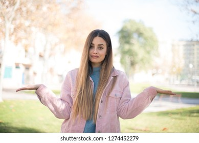 I don't know I don't care, sorry. Attractive funny blond-haired caucasian girl in casual clothes looking aside with puzzled and awkward expression, spreading hands. Standing outdoors.