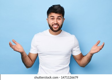 I don't know. close up portrait of confused puzzled handsome bearded young man in white t-shirt standing with raised arms , open palms, isolated on blue background.
