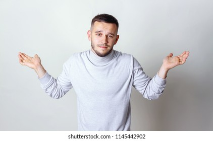 I don't know concept. Portrait of a young man who do not understand what is happening. Man in white turtleneck raises hands and shrugging his shoulders on a gray background copy space