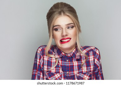 I don't know. confused blonde beautiful girl with pink checkered shirt, collected updo hairstyle and makeup standing and looking away with doubtful face. studio shot, isolated on gray background.