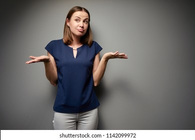 Don't know, Confused young woman against grey wall.