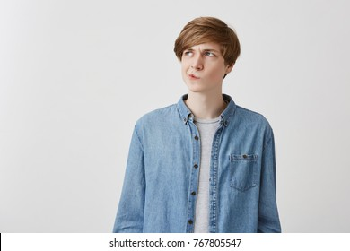 I don't know. Doubtful caucasian young male wearing denim shirt, pouting lips and looking up with indecisive expression on his face, showing doubt and hesitation. Body language and face expression
