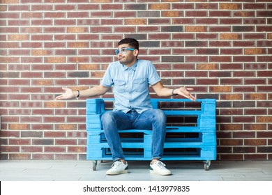 I don't know. Full length portrait of confused handsome young bearded man in casual style and eyeglasses sitting on blue wooden pallet, looking away and puzzled. indoor studio shot on brown brick wall